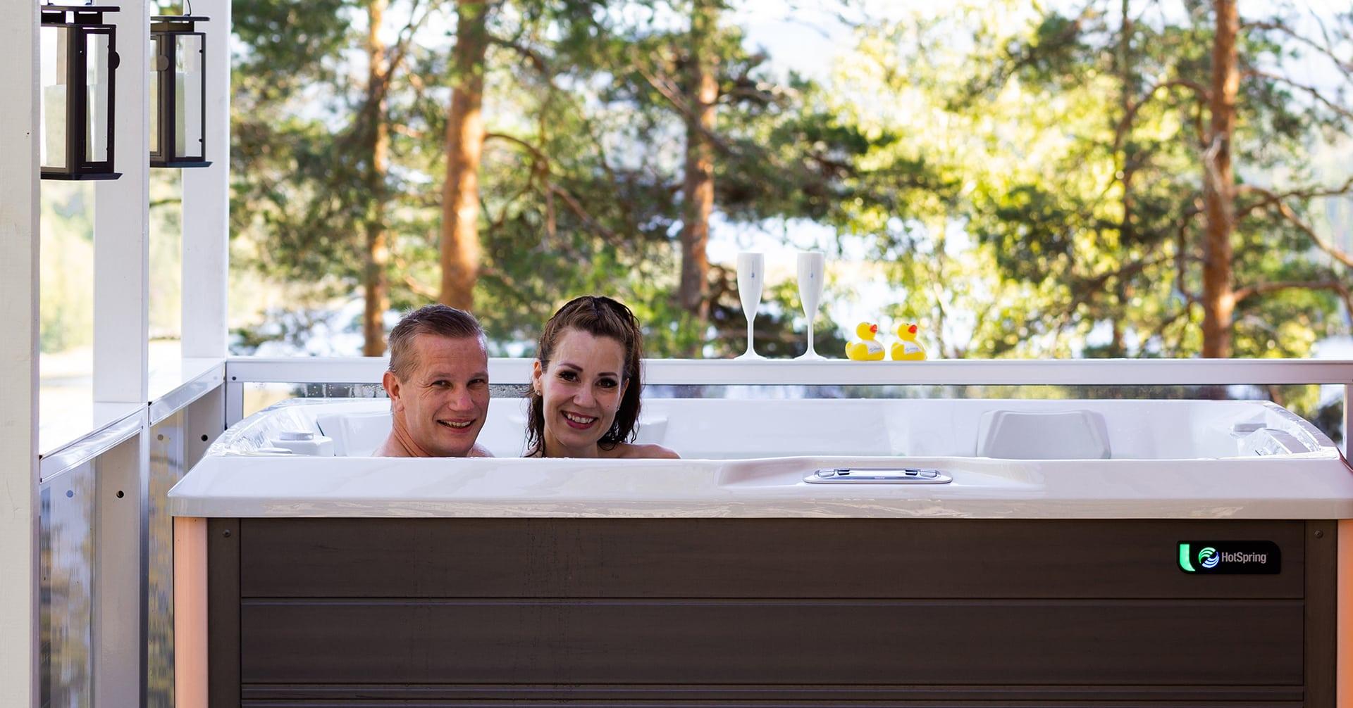 Ulkoporeallas terassilla ja altaassa istuu hymyilevä pariskunta